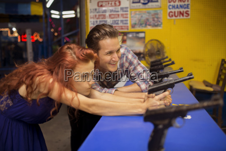 young couple playing shooting game at