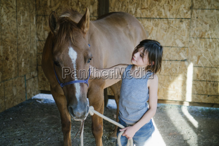 girl petting horse while standing at