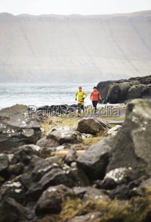friends jogging on footpath by coastline