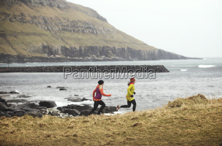 female friends jogging on field against