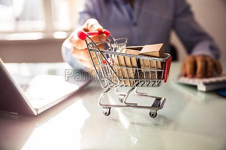 businessperson es hand holding warenkorb