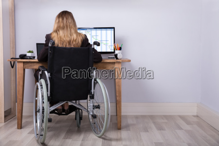 behinderte geschaeftsfrau die an computer arbeitet