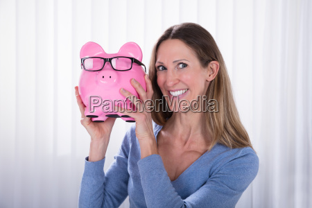 smiling woman holding piggybank