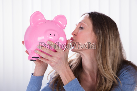 mature woman kissing piggybank
