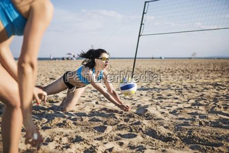 weibliche freunde spielen volleyball am strand