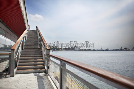 staircase by river in city against