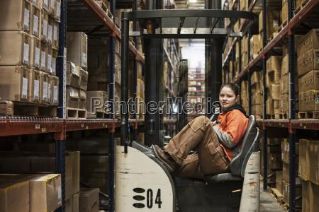 caucasian female warehouse worker sitting in