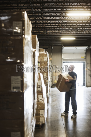 caucasian male warehouse worker checking