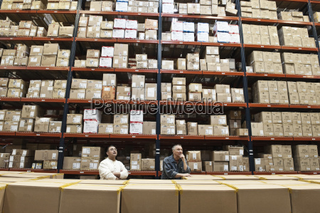 two male warehouse workers checking inventory