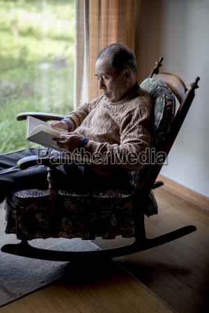 elderly man sitting in rocking chair