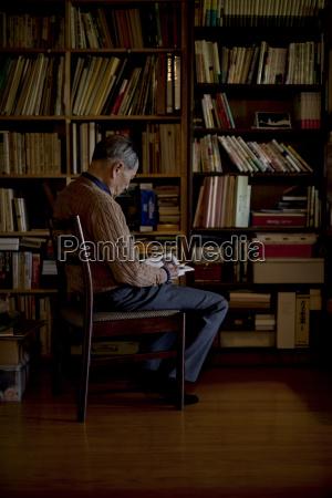 elderly man sitting on chair in