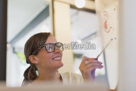 smiling female designer examining transparency diagram