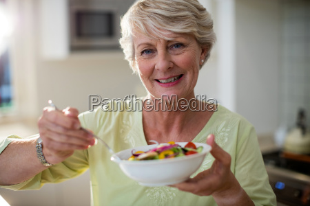 senior woman holding vegetable salad in