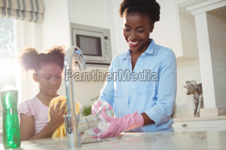 mother assisting her daughter in cleaning