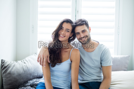 portrait of couple sitting on bed
