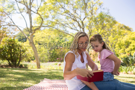 mother and daughter reading novel in