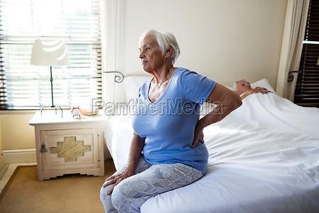 aeltere frau die unter rueckenschmerzen im