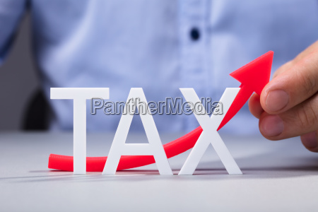 persons hand touching red increasing tax