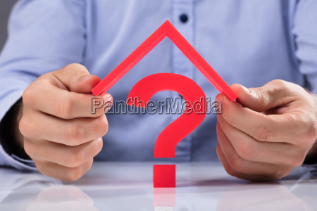 businessperson holding roof over question mark