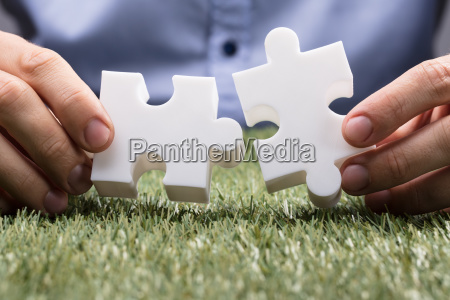 person connecting two white jigsaw puzzle