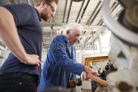 aelterer ingenieur der ausruestung zeigt um