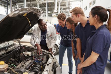 mechaniker der kursteilnehmer um den motor