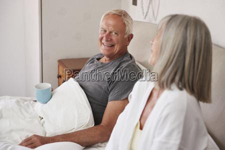 retired couple wearing pajamas sitting in