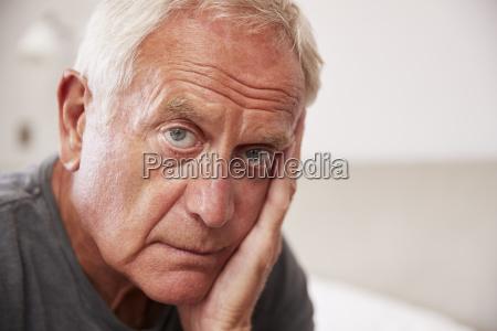 senior man sitting on bed at