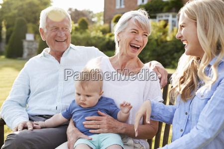 grosseltern sitzen im freien mit baby