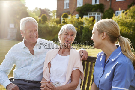 nurse talking to senior couple in