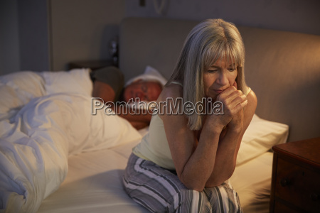 worried senior woman in bed at