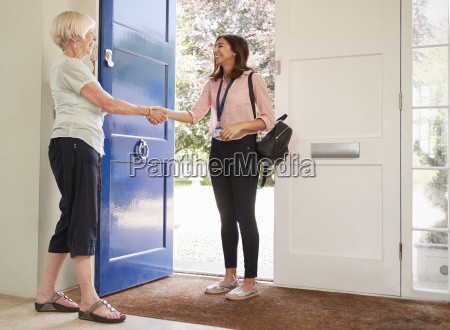 senior woman greeting female care worker