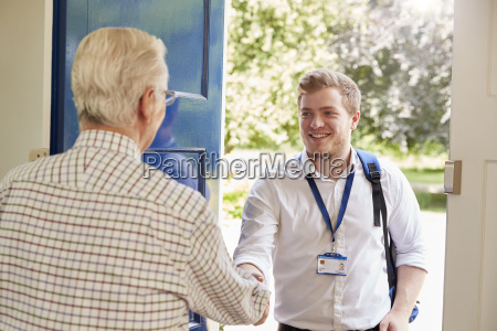 senior man greeting male care worker
