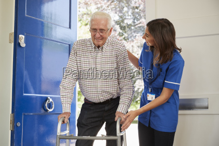 nurse helps senior man using walking