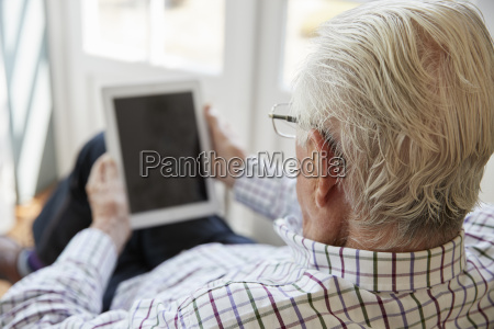 senior man using tablet computer at