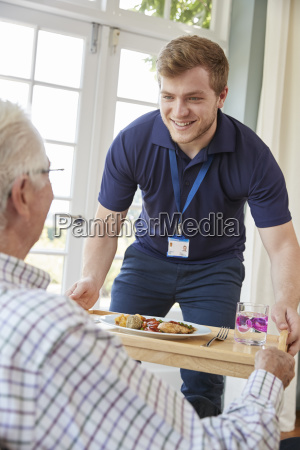 male care worker serving dinner to