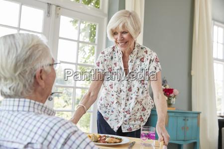 senior woman serving dinner to senior