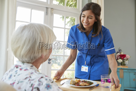 care nurse serving dinner to a
