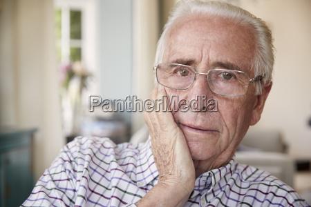 worried senior man at home looking