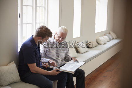 senior man sitting looking at photo