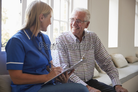 senior man sits with nurse making