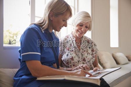senior woman sitting looking at photo