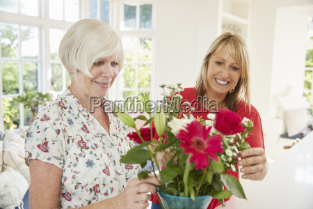 senior woman and adult daughter arranging
