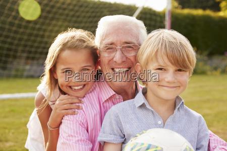 senior man and grandchildren holding ball