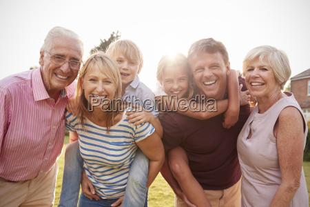 familie mit mehreren generationen im gartenlaecheln
