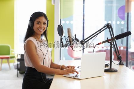 junge mischrassefrau die einen podcast laechelt