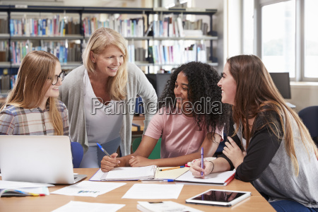 woman teacher working with female college