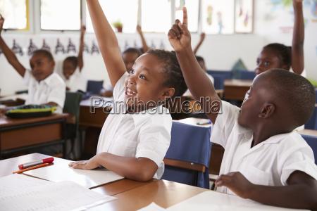 kids raising hands during elementary school