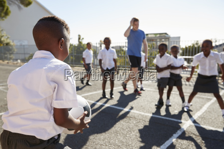 teacher plays football with young kids