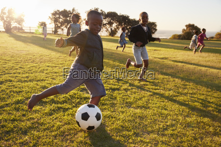 elementary school kids playing football in